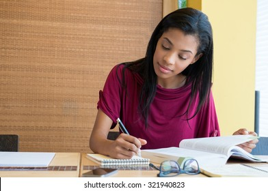 Closeup shot of young woman taking down note in diary. Female student preparing note for the exam. Concentrated girl studying on a book and taking down note sitting at the desk.
