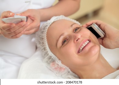 Close-up shot of a young woman talking on the phone at beauty treatment salon while her beautician checking information on cosmetic tube