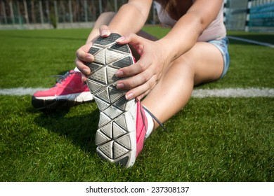 Closeup shot of young woman warming up on grass before running