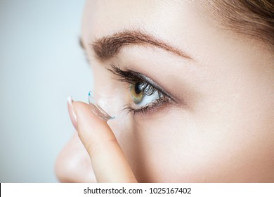 Close-up shot of young woman wearing contact lens.