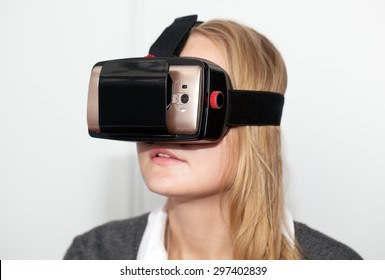 Close-up shot of a young woman wearing VR-headset with smart phone. Getting into virtual space with modern technologies