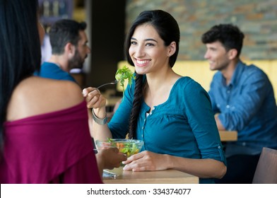 Closeup shot of young women eating salad at restaurant. Happy female friends smiling and chatting. Portrait of smiling girl holding a forkful of salad during lunch break.