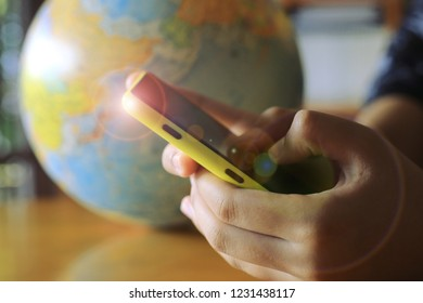 Close-up shots of hand holding mobile phone search knowledge The globe is the background selective focus and shallow depth of field
