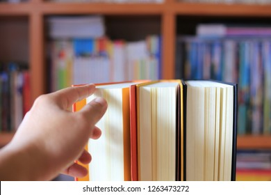Close-up shots of hand reaching to hold books placed on a table in a library. Bookshelf is the background selective focus and shallow depth of field