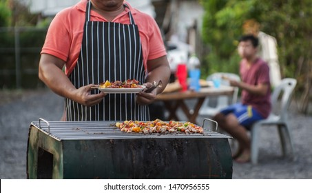 Close-up shots of a man doing a barbecue to celebrate with friends in the evening.