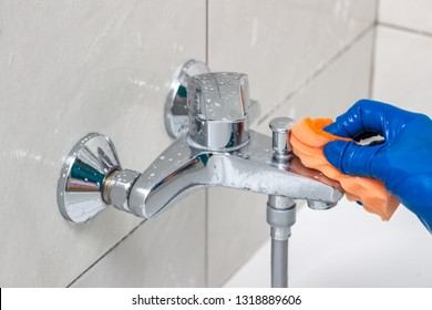 Close-up of the shower faucet and showerhead cleaning process from lime scale, white chalk sediment and stains using a commercial soap scum remover. Bathroom cleaning and disinfection