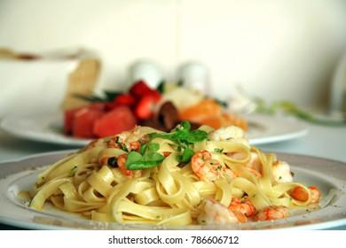 Close-up of shrimp pasta dish with a fruit salad dessert