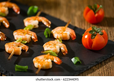 Closeup of shrimp skewers with tomatoes and herbs on a stone