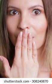 Closeup of shy speechless amazed woman girl covering keeping mouth shut with hand.