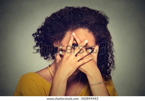 Closeup shy woman hiding face timid. Cute young caucasian woman peeking though hands. Gray background.