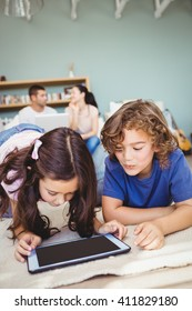 Close-up of siblings using digital tablet while parents in background