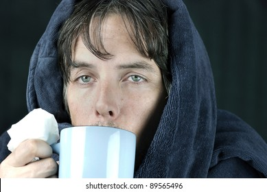 Close-up of a sick man holding a tissue drinking from a hot mug.