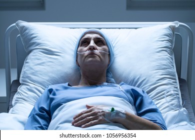 Close-up of a sick, middle-aged woman with breast cancer dying alone in a hospital bed
