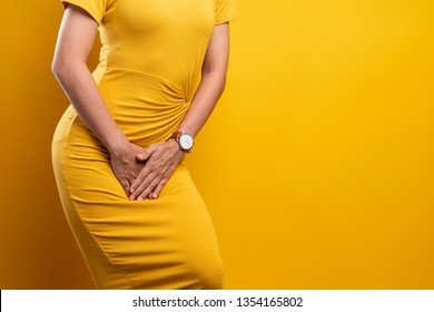 Closeup sick woman with hands holding pressing her crotch isolated on background