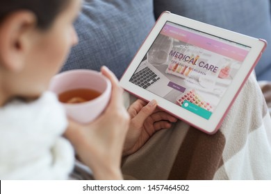 Close-up of sick woman sitting under blanket on sofa and using tablet while reading how to cure cold