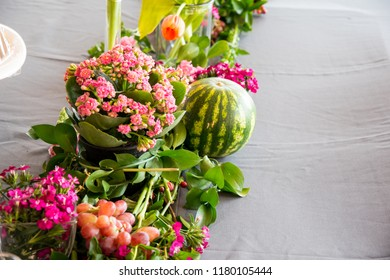 A close-up, side and birds eye view of a floral arrangement of colourful pink bunch in foreground with an enticing round watermelon & grapes. Lovely clear view of a kaleidescope of fresh green leaves