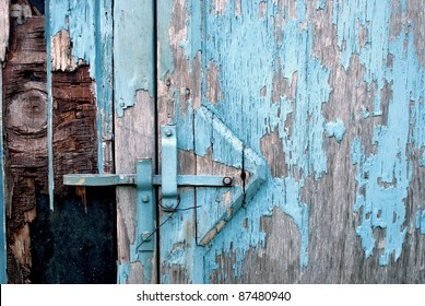 Closeup of the Side of a Blue Shed with Grey Weather-Worn Wood and Peeling Paint That Has Room for Text or Copy.