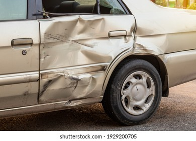 Close-up of a side door of a golden Bond car that was demolished in a collision accident with another vehicle.