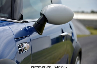 Close-up of the side mirror of a blue and white car