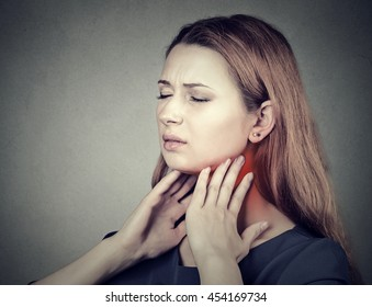 Closeup side profile girl with sore throat touching her neck colored in red. Sick young woman having pain in her throat isolated on gray wall background
