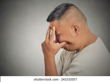 Closeup side profile portrait sad bothered stressed middle aged man holding head with hand really depressed about something isolated grey background. Negative human emotion facial expression feeling