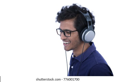 Close-up side snap of a young man wearing eyeglasses and blue t-shirt, enjoy listening to music on his headphones. Isolated on white background.