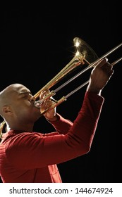 Closeup side view of an African American man playing the trombone against black background
