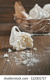 Closeup side view of broken meringue with crumbs and lot of meringues in iron bowl on dark wooden background