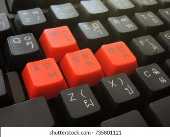 Close-up side view of a computer  keyboard with English and Thai alphabets.