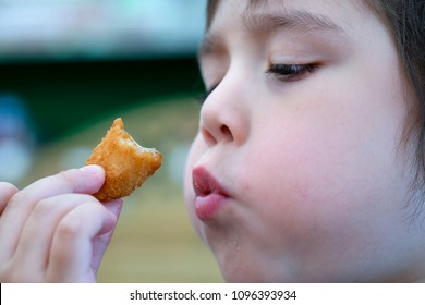 Closeup side view of cute little boy blowing hot scampi on his hand, Selective focus of Child eating scampi, Head shot of kid cooling down his food