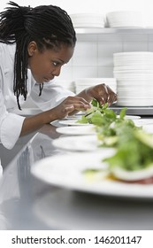 Closeup side view of a female chef preparing salad in kitchen