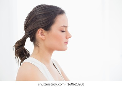 Close-up side view of a fit young woman with eyes closed against white background