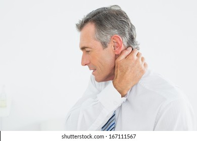 Close-up side view of a mature man suffering from neck pain over white background