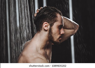 Close-up side view photo of a young man taking a shower. health concept