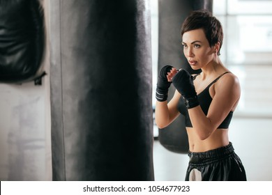 closeup side view photography of huge blcak boxing bag and sportswoman with clenched fists behind it. fan of kickboxing