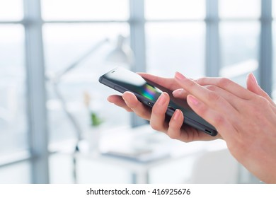 Close-up side view picture of female hands holding smartphone, using apps and wi-fi internet, reading messages.