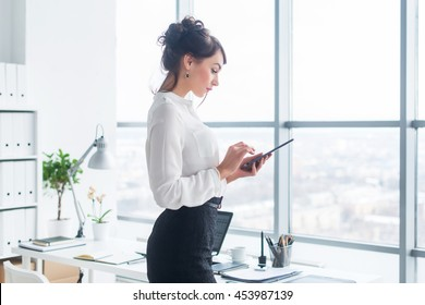 Close-up side view portrait of an employee texting, sending and reading messages during her break at the workplace