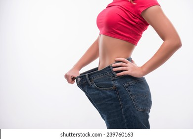 Close-up side view portrait of slim waist of young woman in big jeans showing successful weight loss, isolated on white background