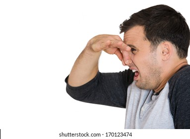Closeup side view portrait of young man, disgust on his face, pinches his nose, something stinks, very bad smell, situation, isolated on white background. Negative emotion facial expression feeling