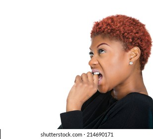 Closeup side view portrait young unhappy, scared woman anxious female biting nails looking with craving, envy for something, worried, isolated white background. Human face expressions, emotion feeling