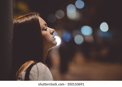 Closeup side view portrait of young sad thoughtful woman leaning against street lamp at night on bokeh copy space background