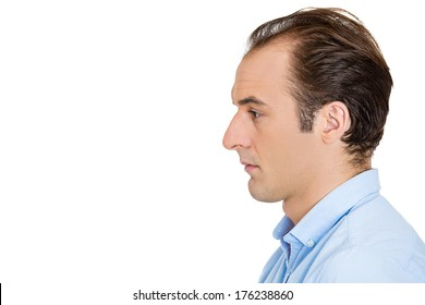 Closeup side view profile head shot portrait of sad bothered stressed serious young man depressed about something or someone, isolated white background. Negative emotion facial expression feeling