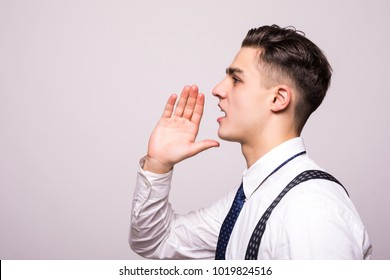 Closeup side view profile portrait, angry upset young man, worker, employee, business man, hand to mouth, open mouth yelling, isolated white background.