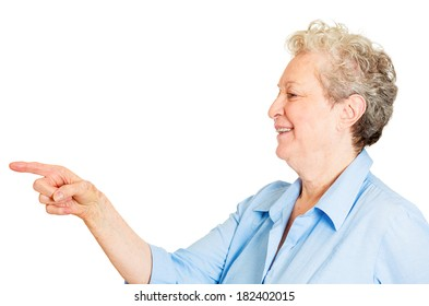 Closeup side view profile portrait of senior mature woman laughing pointing finger at someone or something, isolated white background. Positive emotion facial expression feelings, attitude, reaction