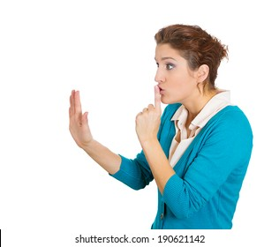 Closeup side view profile portrait, young woman placing fingers on lips with shhh sign symbol, isolated white background. Negative emotions, facial expressions, feelings, body language, reaction
