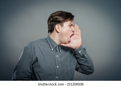 Closeup side view profile portrait, angry upset young man, worker, employee, business man, hand to mouth, open mouth yelling, isolated white background. Negative emotion facial expression emotion