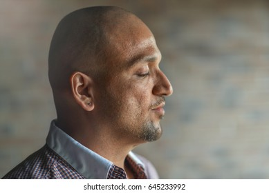 Closeup side view profile portrait of handsome young indian man with his eyes closed, thinking or meditating,