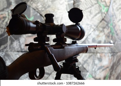 Closeup side view of a rifle on a bipod with camo background.