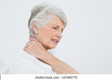 Close-up side view of a senior woman suffering from neck pain over white background