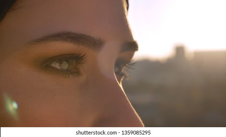 Closeup side view shoot of young attractive female face in hijab with eyes looking forward with urban city on the background